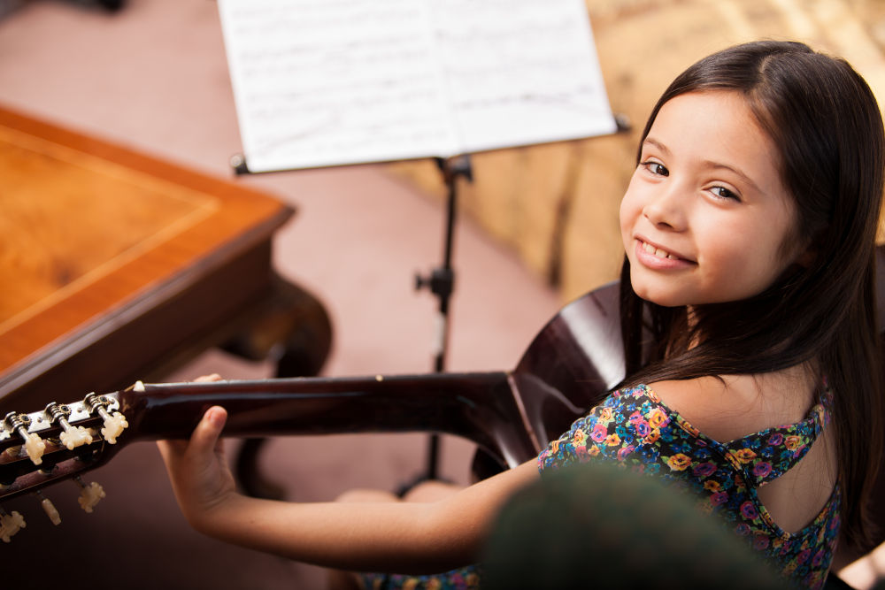 Featured image for Guitar Lessons @ Music Lessons West Knoxville with Ryan Byrne depicting young girl smiling up at camera sitting down and holding a classical guitar in front of a music stand with sheet music on it.