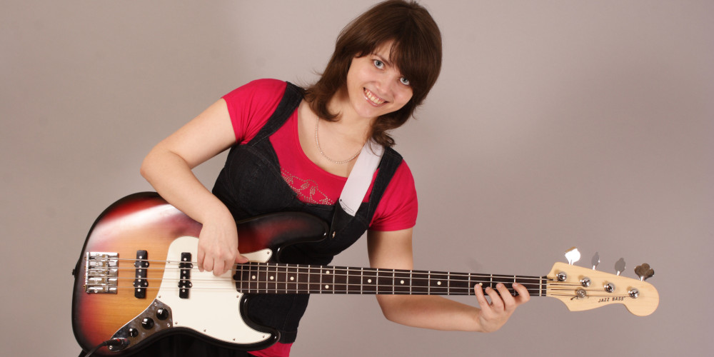Featured image for Bass Lessons at Music Lessons West in Knoxville TN depicting young woman playing a sunburst colored 4-string jazz bass guitar