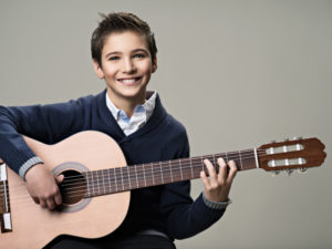 Featured image for Summer Recital 2019 - Music Lessons West depicting smiling teen boy in nice collared shirt and sweater playing a nylon string classical guitar.