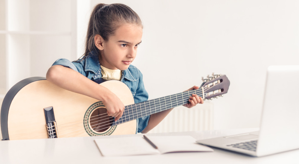 Featured image for article about online music lessons depicting young girl practicing classical girl while looking at the screen of a laptop computer.