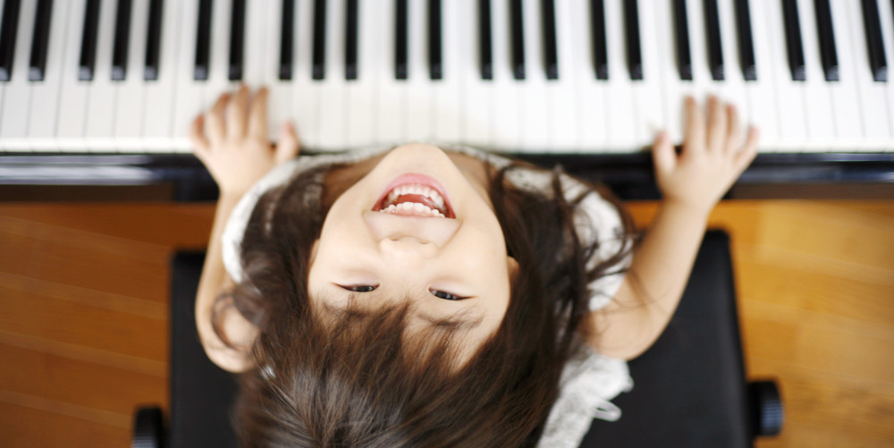 Featured image for Piano Lessons page on Music Lessons West dotcom depicting young girl looking up at camera and smiling while playing piano.