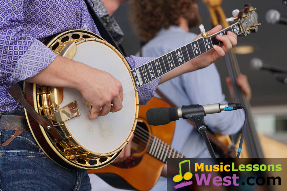 Featured image for Banjo Lessons page on MusicLessonsWest.com depicting banjo player with other acoustic musicians.