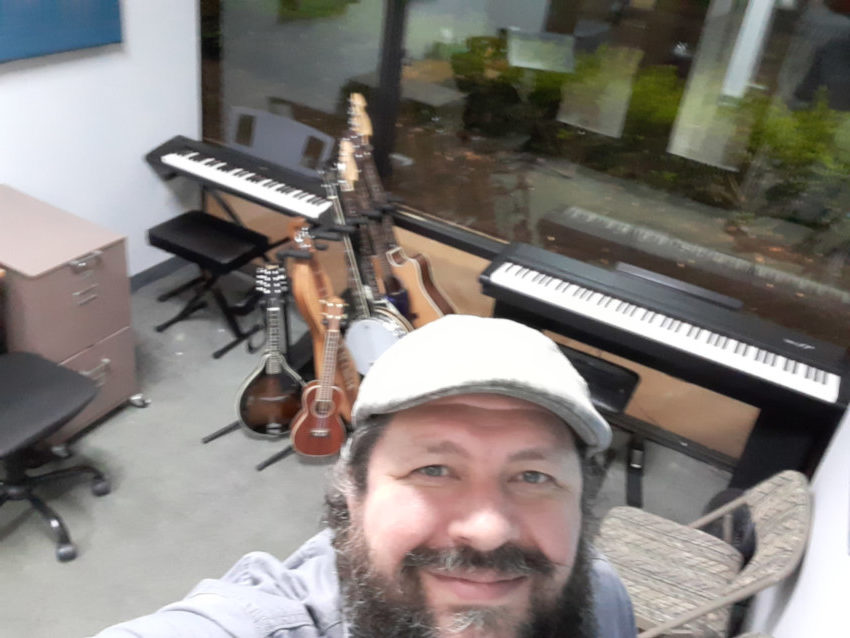 Selfie of music instructor Ryan Byrne standing in his new studio with lots of musical instruments behind him.