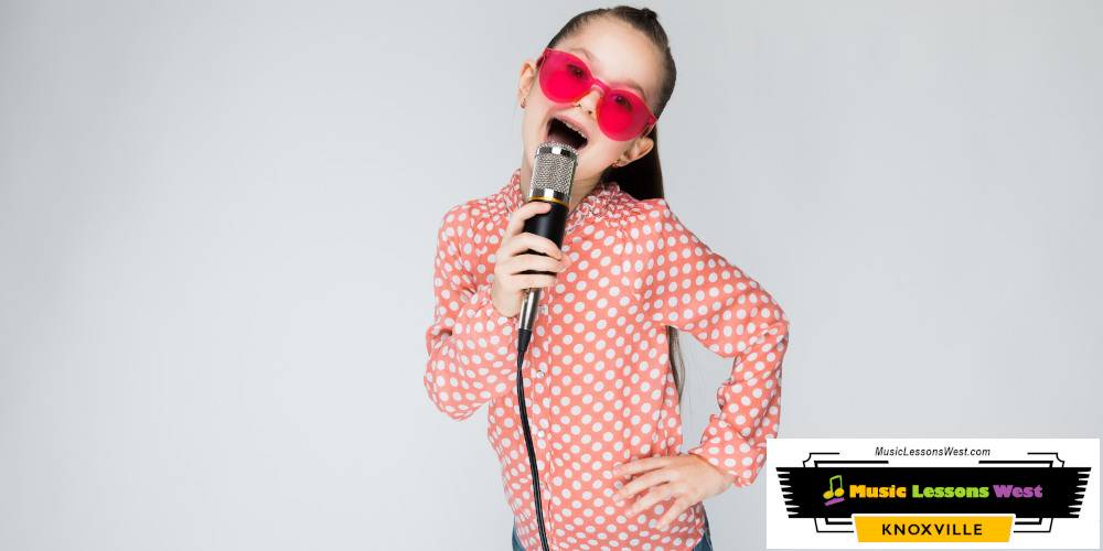 Featured image for Singing Lessons page on MusicLessonsWest.com depicting young girl with bright pink sunglasses singing into a microphone.