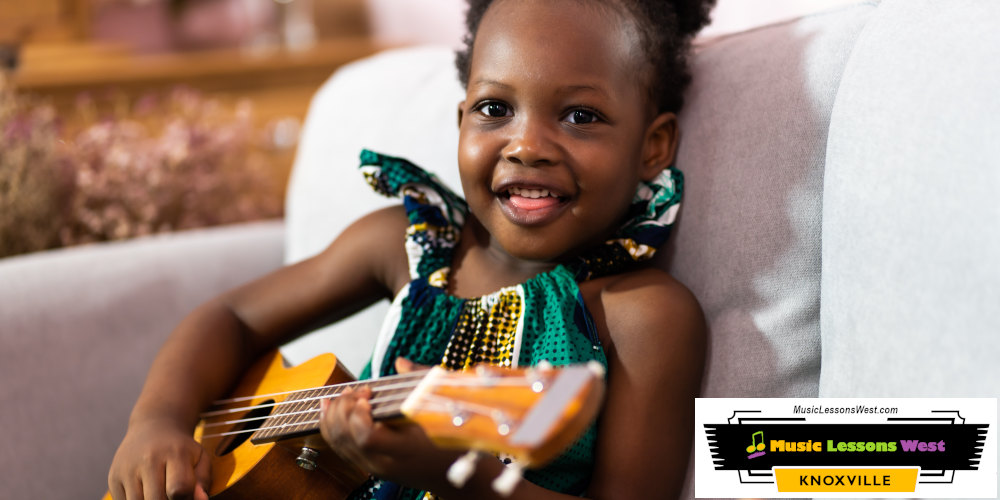 Featured image for Ukulele Lessons page on MusicLessonsWest.com depicting young girl sitting on couch and smiling while strumming on a ukulele.